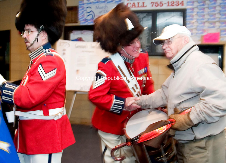 WATERBURY, CT- 15 APRIL 07- 041507JT02- <br /> At right, Staff Sgt. Robert Pettinicchi of the Second Company Governor's Foot Guard Band quickly greets Gene McMahon of Thomaston as Pettinicchi follows Cpl. Steve Kenny, left, into the auditorium at Kennedy High School to begin Sunday's concert, which was hosted by the Republican-American. <br /> Josalee Thrift Republican-American
