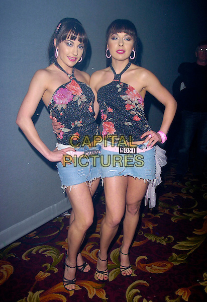 THE CHEEKY GIRLS - MONICA & GABRIELA IRIMIA.At The Mad Hatters Tea Party, Grosvenor House, Park Lane, London, England, January 28th 2007..full length twin sisters black floral patterned halterneck top pink flowers denim mini skirts hands on hips.CAP/CAN.©Can Nguyen/Capital Pictures