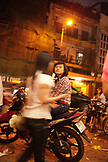 VIETNAM, Hanoi, a young woman waits on her moped while her boyfriend buys ice cream, downtown Hanoi