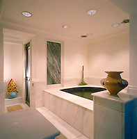 A marble-lined jacuzzi is situated in an alcove adjacent to the swimming pool