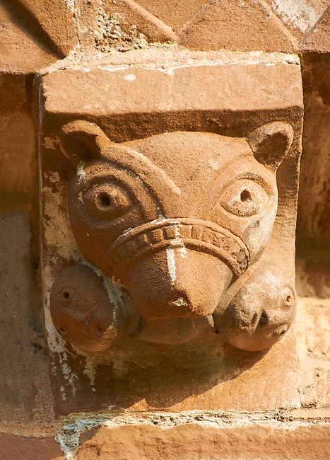 Norman Romanesque exterior corbel no 30 - sculpture of of a muzzled bears head with two humans in its mouth, their heads poking out either side of its head.  The Norman Romanesque Church of St Mary and St David, Kilpeck Herefordshire, England. Built around 1140