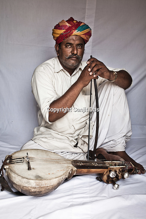 45-year-old Manganiyar artist and Kamancha player, Ghewar Khan poses for a portrait inside his house in Hamira village of Jaiselmer district in Rajasthan, India. Photo: Sanjit Das/Panos