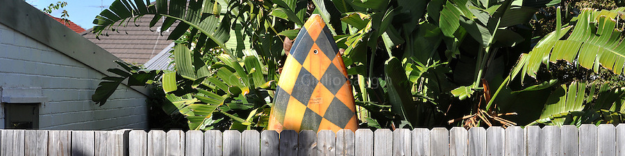 A surfboard leans against a fence in the backyard of a house in Coogee, a seaside suburb of Sydney.