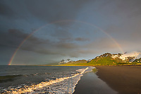 Rainbow over the Aleutian mountain range and the sandy beach shore of Katmai National Park, Alaska Peninsula, southwest Alaska.