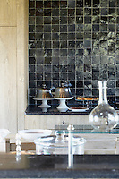 The kitchen work surfaces are topped with dark blue Belgian stone and a wall is lined with rough hewn black stone tiles