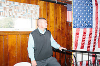 A security guard looks on as Republican presidential candidate and Ohio governor John Kasich speaks with the media after a town hall campaign event at the Derry VFW in Derry, New Hampshire.