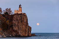 Split Rock Lighthouse in the last light of the day as a full moon rises over Lake Superior at Split Rock Lighthouse State Park on the north shore of Lake Superior in Minnesota.