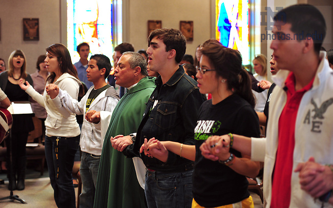 Rev. Joseph Corpora, C.S.C. prays the Our Father with students during the weekly Spanish Mass at St. Edward's Hall Chapel...Photo by Matt Cashore/University of Notre Dame