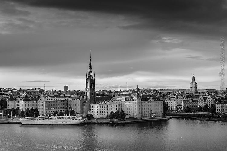 Riddarholmen i skymning med uppklarnande efter häftig regnskur vid Riddarfjärden i Stockholm svartvitt black & white