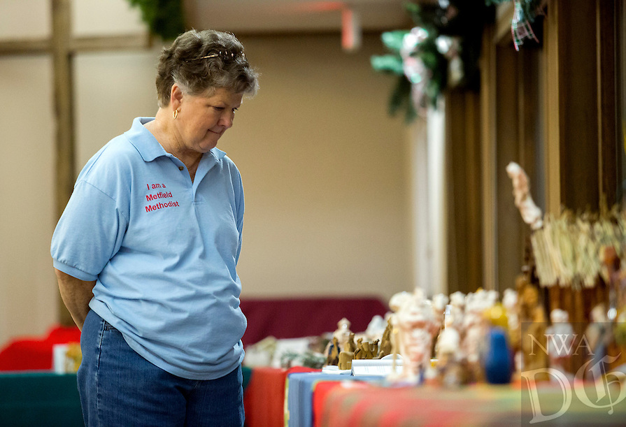 NWA Democrat-Gazette/JASON IVESTER <br /> Vicki Forrest, a church member, looks over one of the Nativity scenes on Monday, Dec. 7, 2015, inside the First United Methodist Church of Bella Vista. About 70 various Nativity scenes owned by the church's members were on display for the evening.