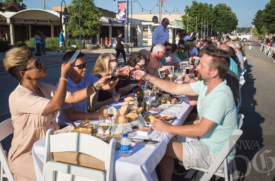 NWA Democrat-Gazette/CHARLIE KAIJO (From front left) Marilin Jerez of Springdale, Ssu-Chi Loh of Springdale and Trent Armstrong of Springdale toast, Saturday, June 9, 2018 on Emma Ave. in Springdale. <br /><br />Back for its 3rd year, this popular event brought hundreds of guests together for a lively, friendly community dinner of multiple courses served under the night sky—right down the middle of Emma Avenue. Past attendees raved about the special experience of dining al fresco with family and friends, as well as meeting new neighbors.