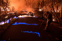 May 2018: A man takes photos while standing between cracks emitting methane gas, identified by its blue color, and surrounded by the Kilauea Volcano eruption in Leilani Estates, Puna, Big Island of Hawai'i.