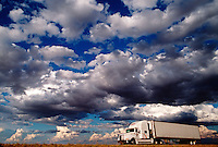 Semi truck on the road under big cloudy sky.