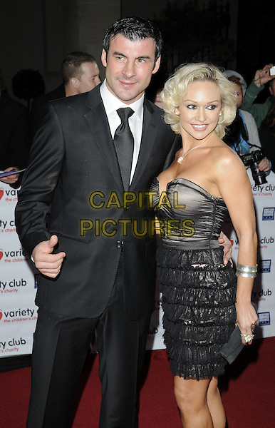 JOE CALZAGHE & KRISTINA RIHANOFF.Variety Club Showbiz Awards held at the Grosvenor House Hotel, Park Lane, London, England. .November 15th, 2009 .half 3/4 length strapless dress black tulle layered tiered ruffle ruffles cleavage clutch bag beige suit couple.CAP/CAN.©Can Nguyen/Capital Pictures.