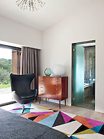 A multi-coloured, geometric patterned rug, from Carpet Diem, retro leather armchair and mid century chest of drawers in the guest bedroom with ensuite bathroom