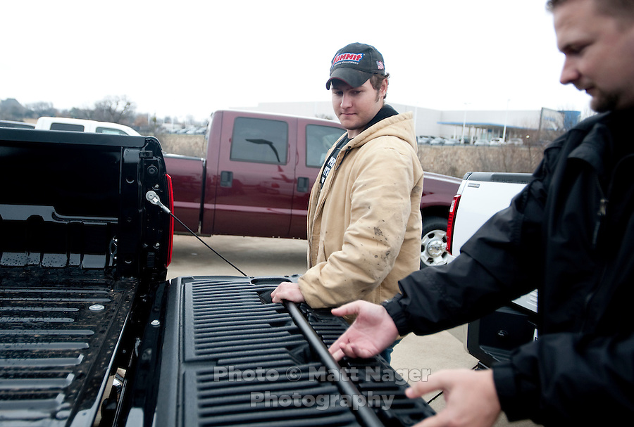 Carl Tanner (cq, left) and Sales Consultant Scott Alter, Jr. (cq) look at a new F250 Ford truck at Bankston Ford in Frisco, Texas, Thursday, Jan., 28, 2009. Ford reported gains in earnings for the first time in four years..Carl Tanner (cq)..PHOTOS/ Matt Nager