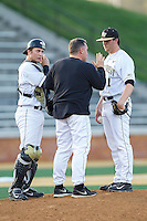 Wake Forest Demon Deacons starting pitcher Matt Pirro (1) and catcher Garrett Kelly (28) listen to pitching coach Dennis Healy (31) during the game against the High Point Panthers at Wake Forest Baseball Park on April 2, 2014 in Winston-Salem, North Carolina.  The Demon Deacons defeated the Panthers 10-6.  (Brian Westerholt/Four Seam Images)