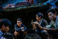 A group eat a meal as they squat beside black cardamom fruit (Thao Qua) being dried on a bamboo rack over a fire. The men are working at a campsite deep in the Hoang Lien Son National Park where the fruits are grown in plantations. After drying the weight of the cardamom is reduced by two thirds making it smaller and easier to pack and transport.