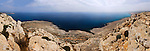 Panoramic view of the Mediterranean Sea, Cape Gkreko, Cyprus. With a young woman sitting alone on the rocks.