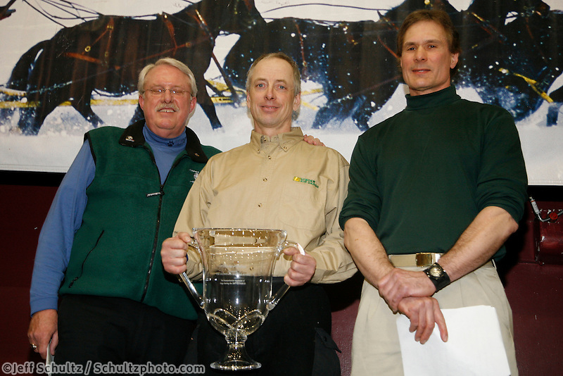 Ed Iten recieves the coveted Leonnard Seppla humanitarian award for dog care from Alaska Airlines vice-president Bill Mckay and chief veterinarian Stu Nelson at the Nome awards banquet.