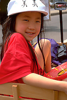 Girl age 6 riding in wagon at Asian American Festival.  St Paul  Minnesota USA