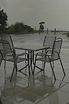 Rain falling on metal chairs and tables, showing couple with umbrella in the background.Birnau, Lake Constance/ Lake Bodensee, Bavaria, Germany.