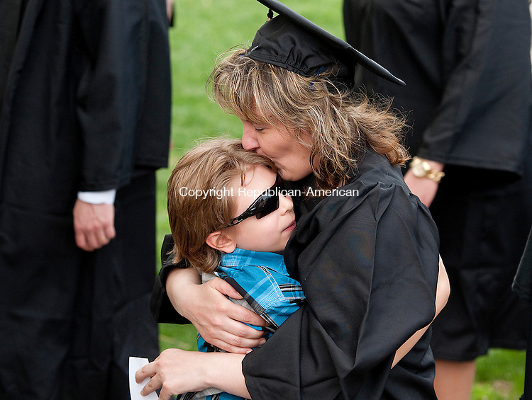 WATERBURY, CT--050915JS05-  Gina Maria Zaiko of Waterbury gets a congratulatory hug from her son Nico Recchia, 7, as she walks with her fellow graduates during the Post University's 2015 Commencement Saturday at Post University in Waterbury. Zaiko received her Bachelor of Science degree in Accounting. <br /> Jim Shannon Republican-American