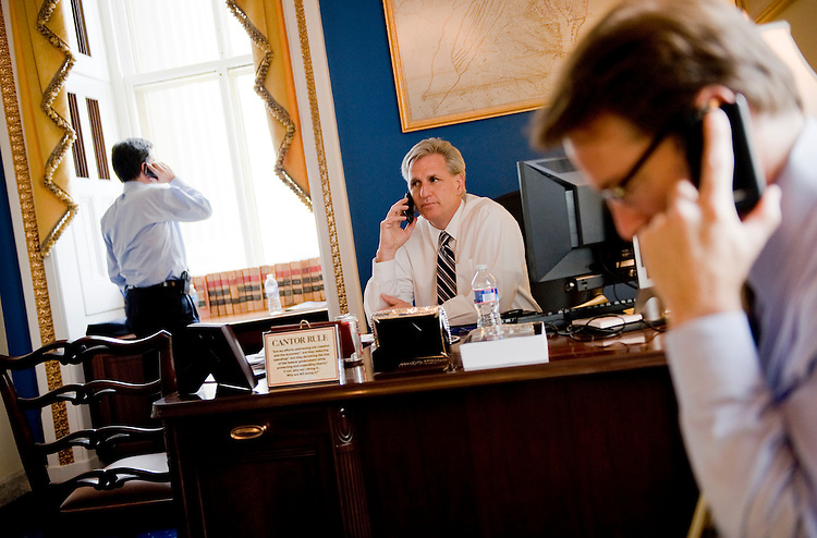 UNITED STATES - AUGUST 01:  From left, House Majority Leader Eric Cantor, R-Va., Majority Whip Kevin McCarthy, R-Calif., and Chief Deputy Whip Peter Roskam, R-Ill., phone members of their caucus from Cantor's Capitol office to see how they will be voting before the debt limit vote in the House, Monday.  (Photo By Tom Williams/Roll Call)