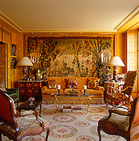 The drawing room is decorated in jewel tones and furnished with antiques upholstered in layers of exotic fabric