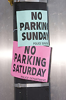 "Signs on a utility pole advising of ""No Parking"" and Saturday and Sunday due the 9/11 Memorial Ceremony."