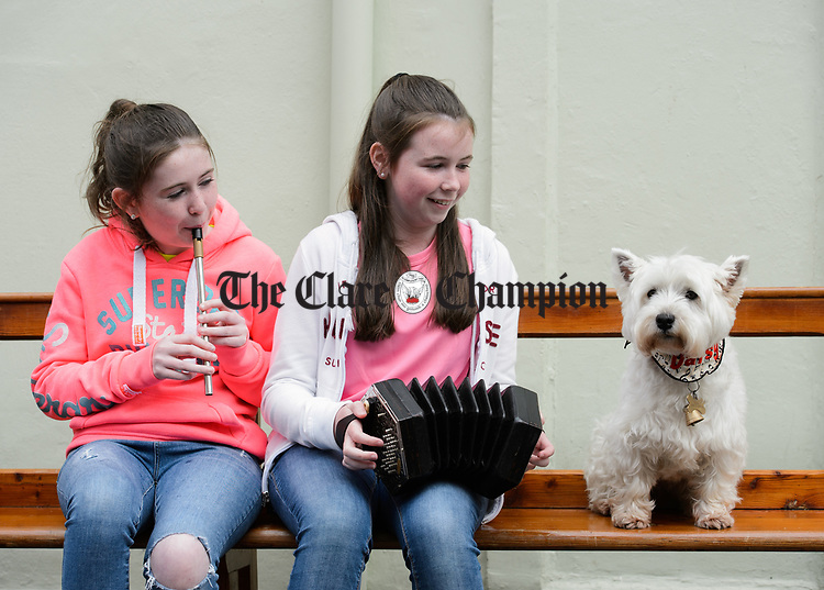 Amy and Leah Scanlan of Inagh perform on O Connell street watched by Daisy during Fleadh Cheoil na hEireann in Ennis. Photograph by John Kelly.