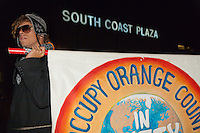 An unknown marcher holds the Occupy Orange County sign while marching at South Coast Plaza early in the morning (1:08am)  on Black Friday.  A lit South Coast Plaza sign is lit in the background.   The protesters were tied together by rope, being led by a single protestor dressed in a suit (as a banker), symbolizing how the 1% lead the 99%.