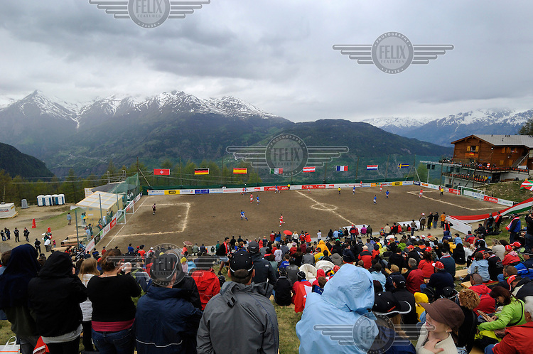 Not to be put off by a little rain making conditions in the stands slippery, supporters watch a match at the other official Euro 2008 football tournament: the European Championship of Mountain Villages. The tournament was held at the summer training ground of hosts FC Gspon, standing at 2008 metres above sea-level,  and surrounded by 4000 metre alpine peaks. It is the highest football pitch in Europe, and reachable only by cable car, or a long walk. Amateur league teams from eight countries took part.