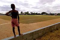 024222.SP.0114.angels20.kc--San Pedro de Macoris, Dominican Republic--Standing on the wall along left field Jonas DeLeon, 10, watches the game between Anaheim Angels Academy Team and the Boston Red Sox Academy Team. At a young age Dominican boys learn that baseball could be their chance to make it big. Local kids are a common sight around the baseball academies run by MLB teams. They provide an all around learning experience for boys once they reach sixteen.