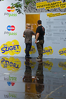 Participants queue in the rain to buy a MetaPay card on Sziget festival held in Budapest, Hungary on August 07, 2011. ATTILA VOLGYI.Metapay is a new card base paying method for the festival goers to skip using cash.
