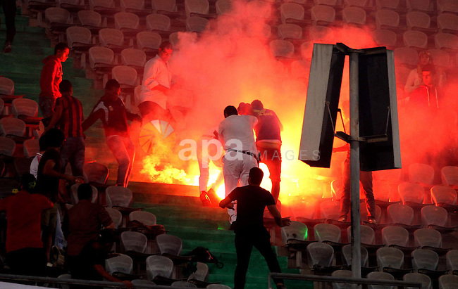 "Egyptian soccer fans known as ""Ultras"" shout slogans against the government and police while holding a flare during the African Nations Cup qualifying soccer match between Egypt and Botswana, in Cairo October 15, 2014. The banner reads, ""Ultras not a criminal, Freedom for fans"". Photo by Amr Sayed"