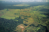 Amazonia, Brazil. Aerial view of Rainforest with large areas cleared for farming and cattle ranching; sawmill in the foreground.
