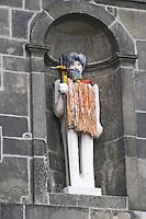 statue in a niche on cais da ribeira porto portugal