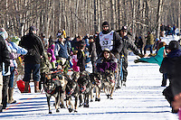 John Baker and team run past spectators on the bike/ski trail during the Anchorage ceremonial start during the 2014 Iditarod race.<br /> Photo by Britt Coon/IditarodPhotos.com