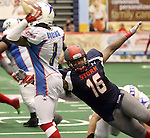 SIOUX FALLS, SD - JUNE 7 James Dunlap #16 from the Sioux Falls Storm reaches out to bring down quarterback Jerell Norton #3 from the Texas Revolution in the second quarter of their game Saturday night at the Sioux Falls Arena. (Photo by Dave Eggen/Inertia)