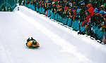 The crowd cheers on a racer as he makes his way down the skeleton course during competition at Utah Olympic Park.