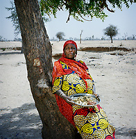 Ramata Modou, 58, holds a meal of ground red maize, white rice and crushed mango leaves. This will be the only food she and her six children will eat today. It was gathered by begging from house to house in a village near the IDP camp where they live and where Ramata is the appointed leader. <br /> &nbsp;<br /> During an attack on her village, on the border with Nigeria, Ramata Modou's husband suffered a heart attack and her 17 year old daughter and grandchild were taken. Following the attack Ramata and her children, aged from five to 16 years old, fled their village, eventually arriving in&nbsp;Meme,&nbsp;where, for the first two months, they all slept under trees. <br /> <br /> Ramata says: 'When the fighters came into the village, my husband started shaking and trembling. He was holding his head. When they arrived, one man was standing at the door with a gun. Another one put his leg on my mattress and the other one was pulling my daughter. My daughter was screaming and I was screaming, but they didn't hit me. Leaving my village was very difficult. We used to own cattle and sheep, but we had to leave all of those things behind. We had no choice, we had to leave. Even the roofs of some of the houses have now been stolen.'