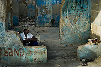 A Haitian man rests in a shadow inside a house ruin in the slum of Cité Soleil, Port-au-Prince, Haiti, 21 July 2008. Cité Soleil is considered one of the worst slums in the Americas, most of its 300.000 residents live in extreme poverty. Children and single mothers predominate in the population. Social and living conditions in the slum are a human tragedy. There is no running water, no sewers and no electricity. Public services virtually do not exist - there are no stores, no hospitals or schools, no urban infrastructure. In spite of this fact, a rent must be payed even in all shacks made from rusty metal sheets. Infectious diseases are widely spread as garbage disposal does not exist in Cité Soleil. Violence is common, armed gangs operate throughout the slum.
