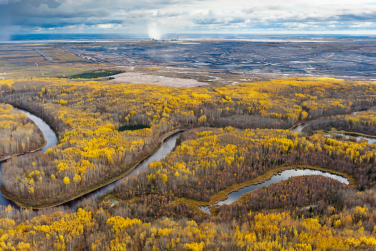 """MacKay River, Boreal Forest, and Tar Mine                                                      Northern Alberta. Canada. 2010.  The Boreal Forests and wetlands that surround the Tar Sands are the most carbon rich terrestrial ecosystem on the planet, holding almost twice as much carbon per acre as tropical rainforests. Referred to by the Tar Sands industry as """"overburden,"""" these forests are scraped off and the wetlands dredged, to be replaced by tar mines like this whihc produce significantly more carbon that traditional oil extraction.     Nikon D3, Nikkor 24-70  f2.8. Shot at 34, iso 800, 1/1250 at f4. Alberta Tar Sands, Northern Alberta, Canada."""