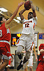 Gejuan Booker #12 of Babylon, right, soars through the air as Emond Frazier #3 of Center Moriches challenges his shot during a Suffolk County League VII varsity boys basketball game at Babylon High School on Friday, Jan. 26, 2018. Center Moriches won by a score of 84-80.