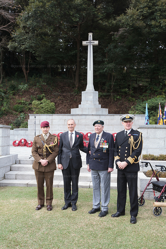 Ex-Japanese prisoner of War, Roy Welland (94) second right) stands to honour the war dead with British Ambassador, Tim Hitchens and armed forces personnel during the Remembrance Day ceremonies at the Commonwealth War Cemetery in Hodogaya, Yokohama, Japan. Wednesday November 11th 2015 Roy Welland is from Colchester in Essex and served with the Royal Berkshire regiment in India in WW2
