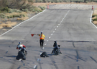 Feb 26, 2016; Chandler, AZ, USA; An NHRA official directs top fuel Harley motorcycle riders off the top end during qualifying for the Carquest Nationals at Wild Horse Pass Motorsports Park. Mandatory Credit: Mark J. Rebilas-