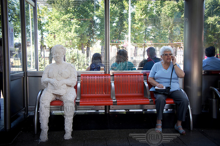 A woman makes a call on a mobile phone while sitting next to 'Waiting', a sculpture by Esther Neslen, placed on a bench in a bus station in Walthamstow, London.
