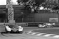MIAMI, FL - MARCH 2: The Hendricks Motorsports Lola T710 HU1/Corvette GTP of  Sarel van der Merwe and Doc Bundy is driven ahead of the Bridgestone/Bayside Porsche 962 109 of Bob Wollek and Paolo Barilla during the Lowenbrau Grand Prix of Miami IMSA GTP race on the temporary street circuit in Bicentennial Park in Miami, Florida, on March 2, 1986.