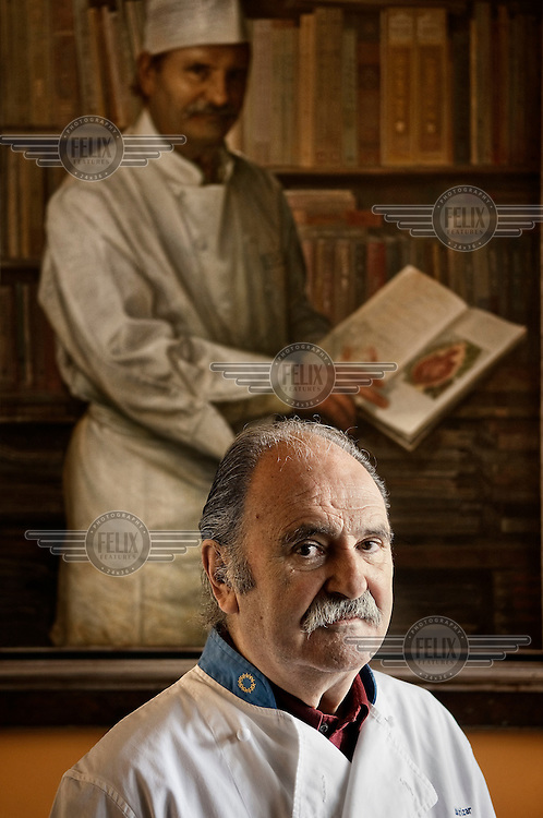 80 year old chef Luis Irizar stands in front of his portrait. He is one of the pioneers of the Basque cuisine and runs a cooking school in San Sebastian.